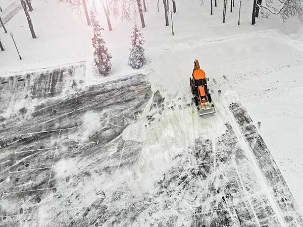 Aerial. Snow removal tractor cleans street from snow.
