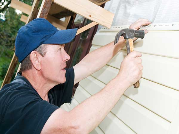 Worker planking house with plastic siding panels