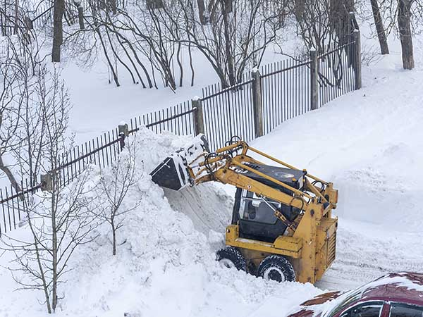 A small city excavator is used for local processing of city roads. Fighting heavy snow.
