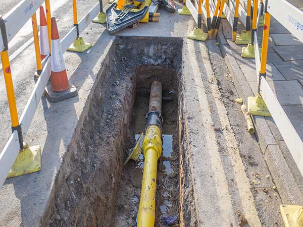 Underground pipe being fixed in trench
